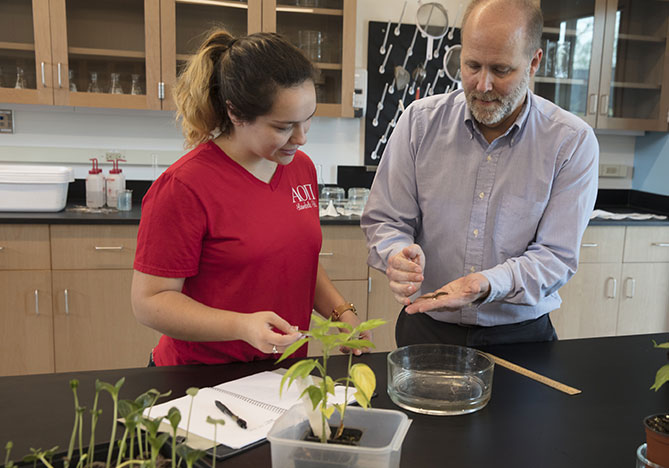 Student and professor in bio lab with plants