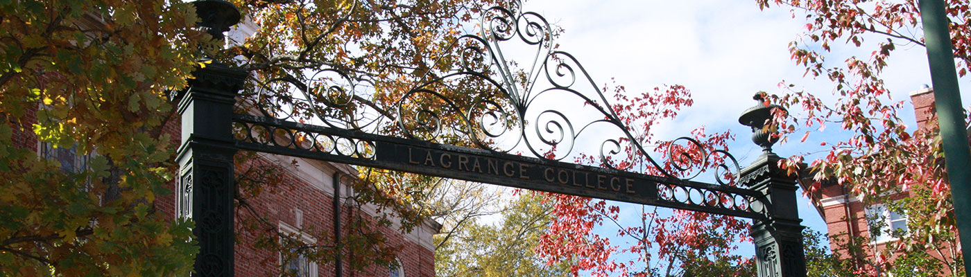 LaGrange College gateway with the sky, campus buildings, and fall leaved trees in the background.