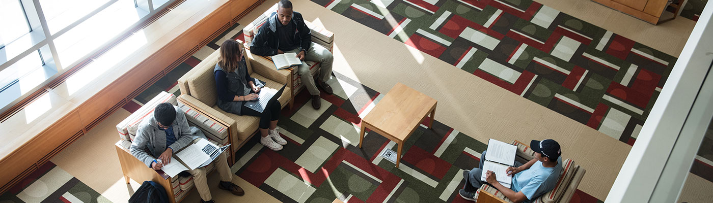 Overhead view of four students on comfy chars studying in the library lobby. Two of them are actively interacting.